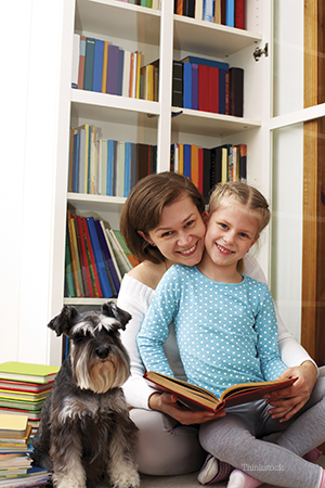 Mom reading to daughter with family dog